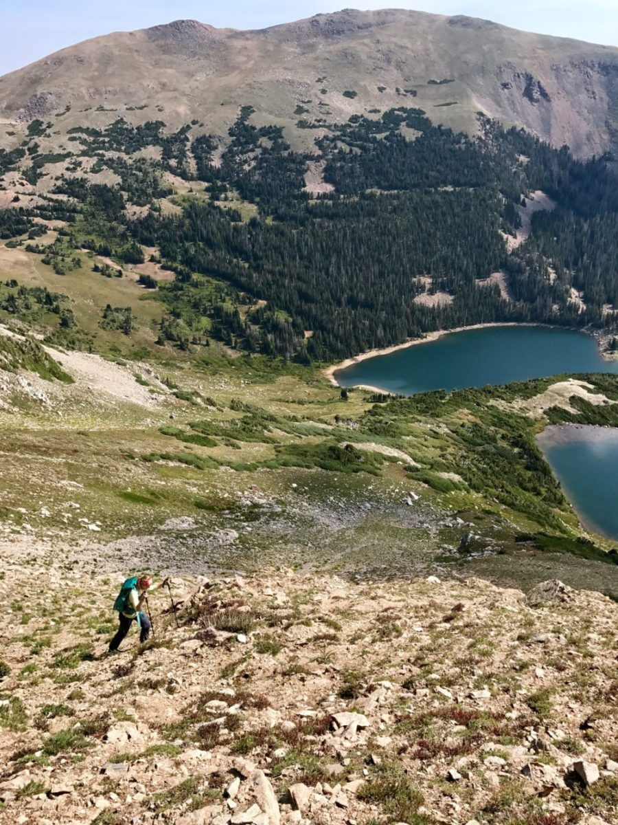 Emily Sehloff backpacking up a climb toward the ridge with Hang Lake, Blue Lake, and Cameron Peak in the background. Photo by Ryan Bettin.